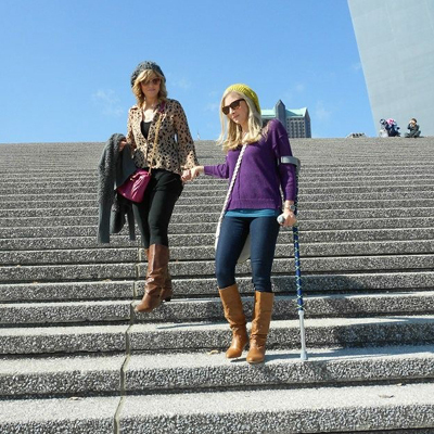 Carly as a young woman going down the stairs from the St. Louis Gateway Arch with crutches and holding a woman's hand