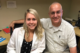 Emily as adult in white coat with Dr. Shawn Standard while doing PA clinical rotation at International Center for Limb Lengthening