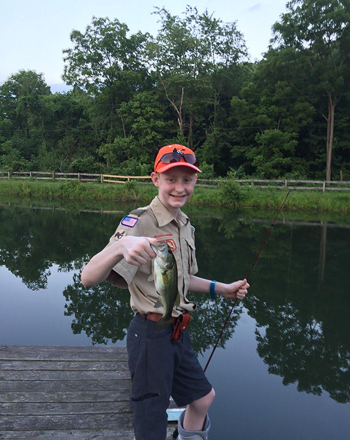 Gary holding up a fish he caught by a lake while wearing a walking boot