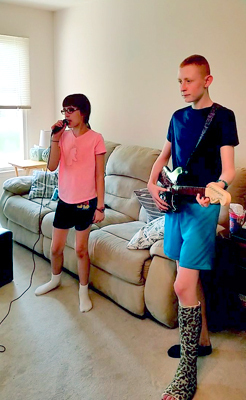 Gary in a leg cast playing electric guitar and his sister with a microphone playing a rock band video game