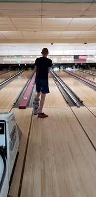 Gary bowling while wearing a walking boot