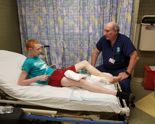 Gary reclining back with leg elevated in clinic bed while talking to Dr. John Herzenberg