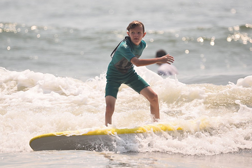 Jeffrey at 10 surfing on a surf board in the ocean