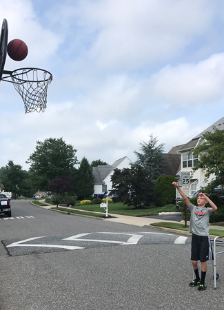 Jeffrey shooting a basket in a basketball hoop on the street with a walker behind him while being treated with a Precice internal nail and 8 plate