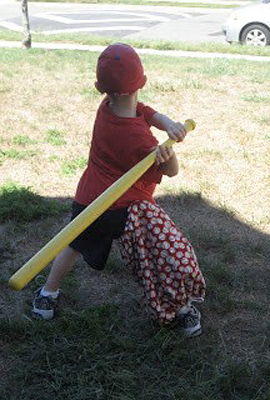 Jeffrey as a young boy wearing an external fixator with a cover from behind and batting playing wiffle ball in a yard