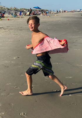 Jeffrey at 10 running on the beach with a towel