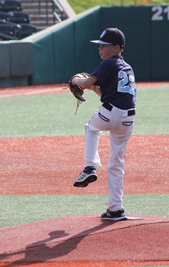 Jeffrey at 11 in baseball uniform winding up for a pitch on a baseball field's pitcher mound