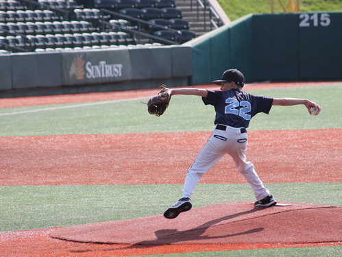 Jeffrey at 11 in baseball uniform pitching on a baseball field's pitcher mound
