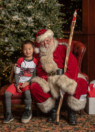 Primo wearing a shoe lift sitting with Santa Claus