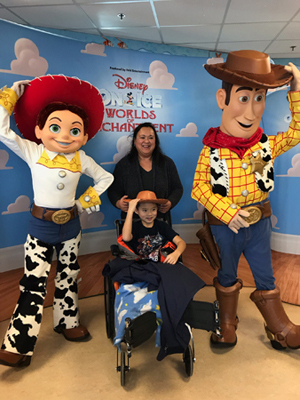 Primo in a wheelchair and his mom enjoying meeting Disney on Ice Toy Story characters visiting Sinai Hospital pediatric patients