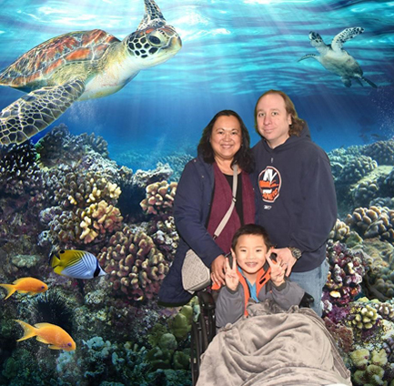 Primo smiling in wheelchair with his parents in front of a National Aquarium backdrop with coral reef, fish and turtles