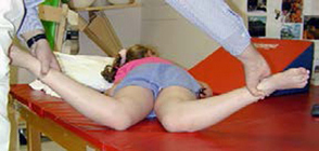 Physical therapist demonstrating the internal rotation of the hip exercise for Perthes on a patient