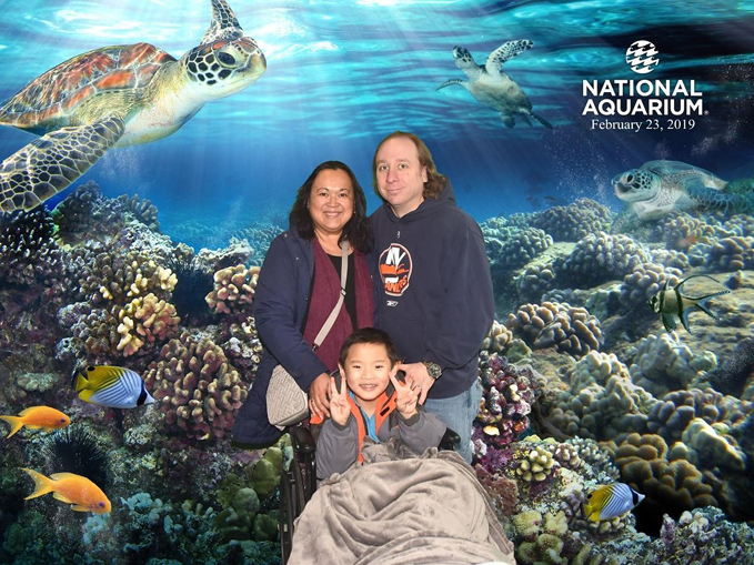 Young boy patient smiling in wheelchair with smiling parents in front of a National Aquarium backdrop with coral reef, fish and turtles