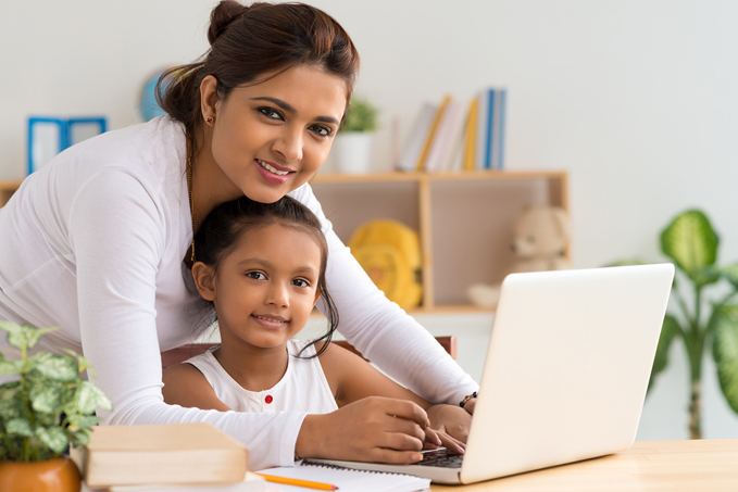 Woman and child smiling while using a laptop