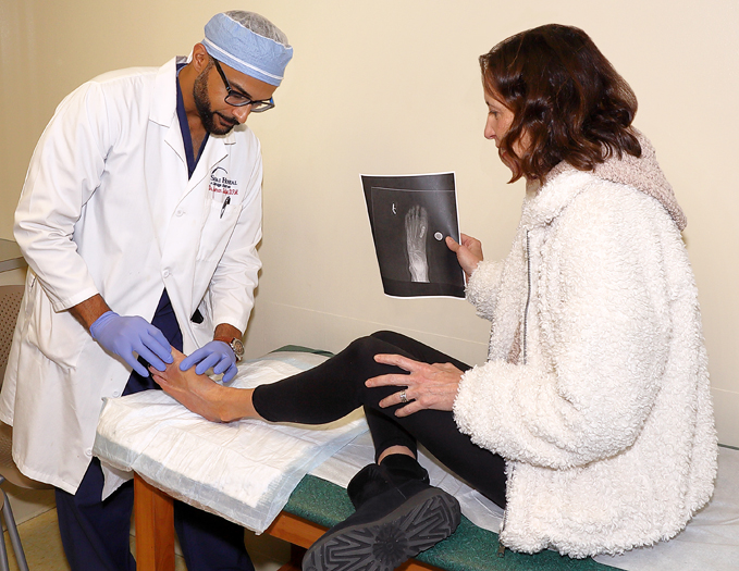 Dr. Noman Siddiqui examining a patient's foot at the International Center for Limb Lengthening while she holds an x-ray of her foot