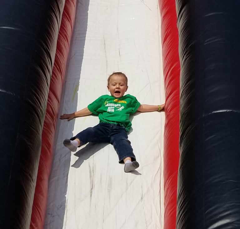 Close up of young child sliding down the giant inflatable slide
