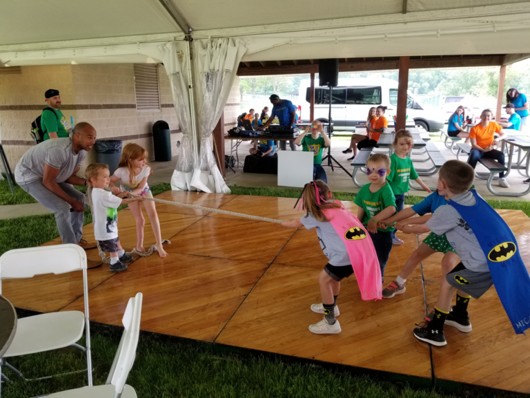 Kids playing tug of war on the dance floor under the tent