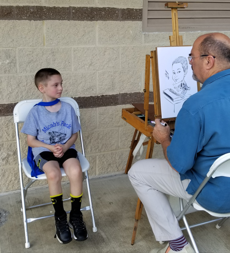A young patient sitting while an artist draws his caricature