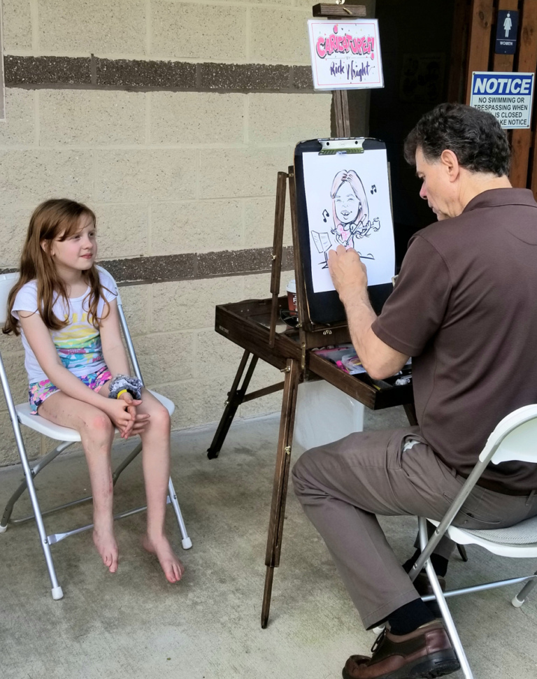 A young patient sitting while an artist draws her caricature