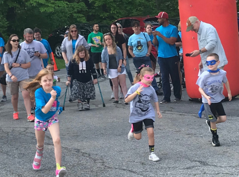 3 children—2 in super hero masks and capes-- racing out in front of the other walk participants