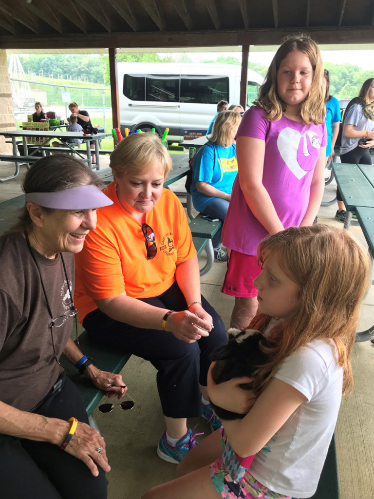 A young girl patient showing the petting zoo rabbit to a former patient and staff member