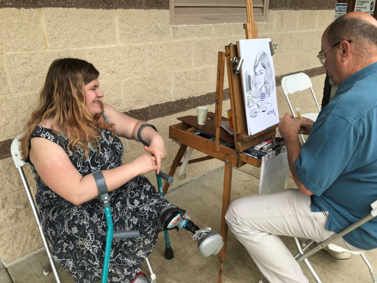 A young patient with crutches sitting while an artist draws her caricature