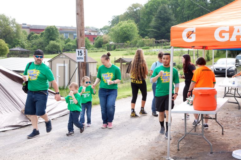 A family of 4 at the walk passing a Gatorade stand