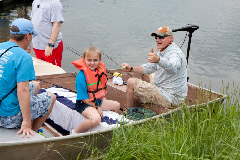 Dr. Shawn Standard giving a thumbs-up sign in a boat with a young girl patient in a life jacket and her father
