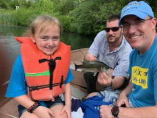 A young girl patient in a life jacket and her father with Dr. Standard's assisting nephew holding up the fish they caught