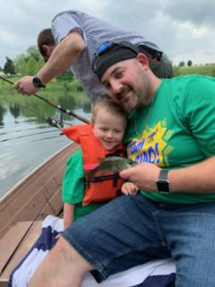 A father and son in a life jacket showing the fish that they caught