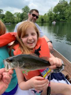 A young girl patient in a life jacket in a boat on a lake showing off the fish that she caught
