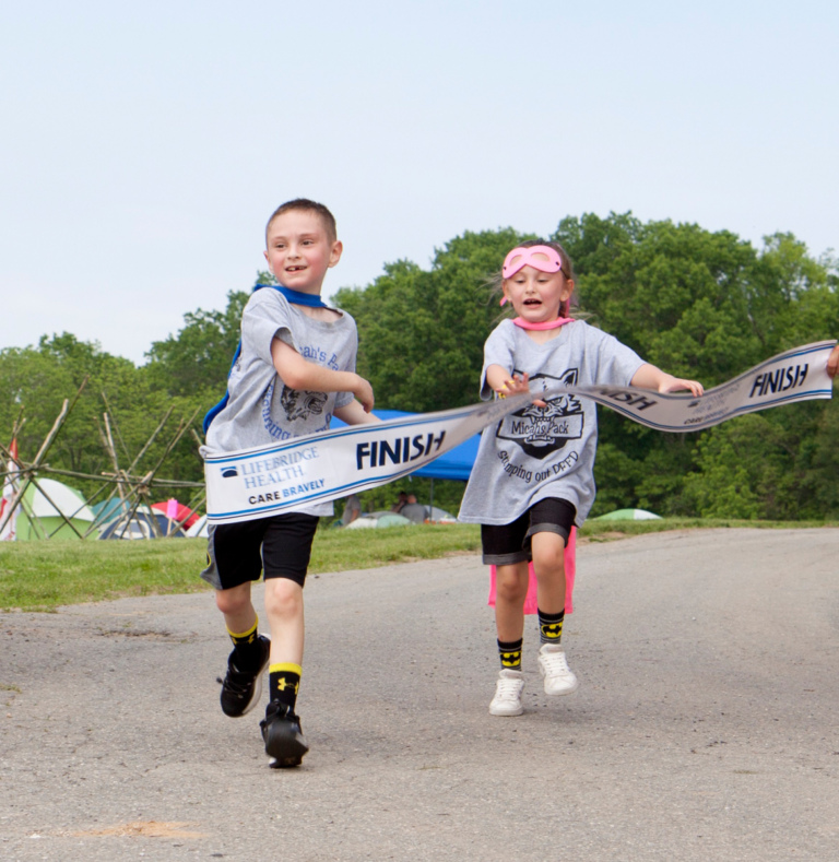 2 children breaking through the walk finish line
