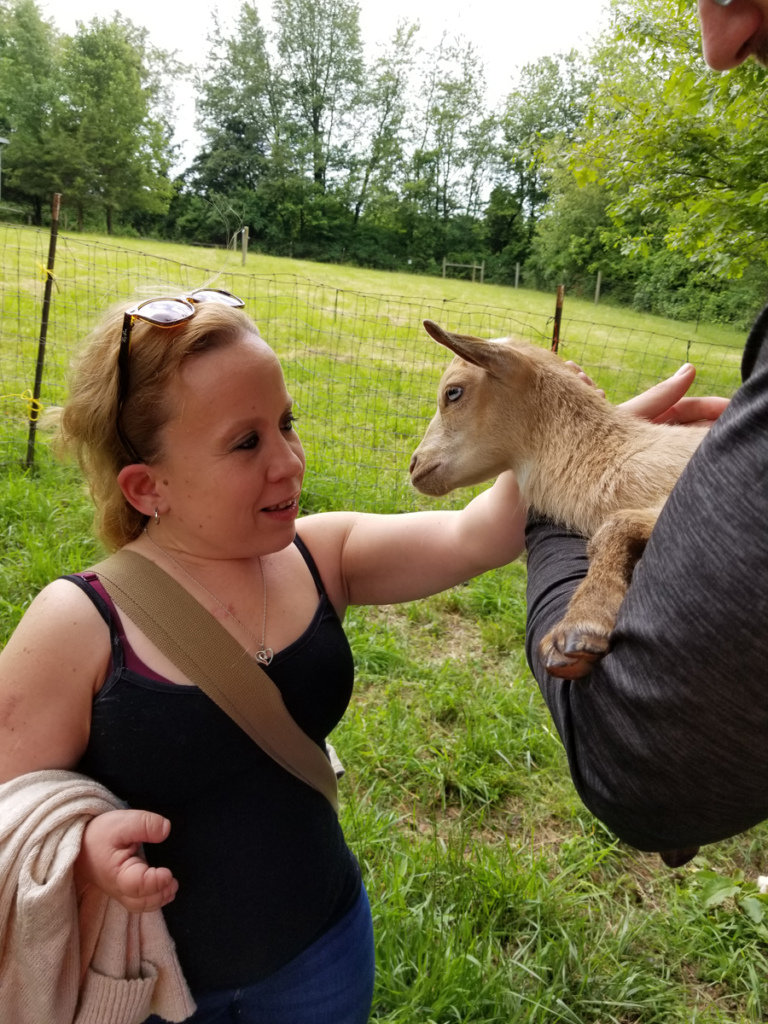 A woman who is a former patient petting a young goat on the farm tour