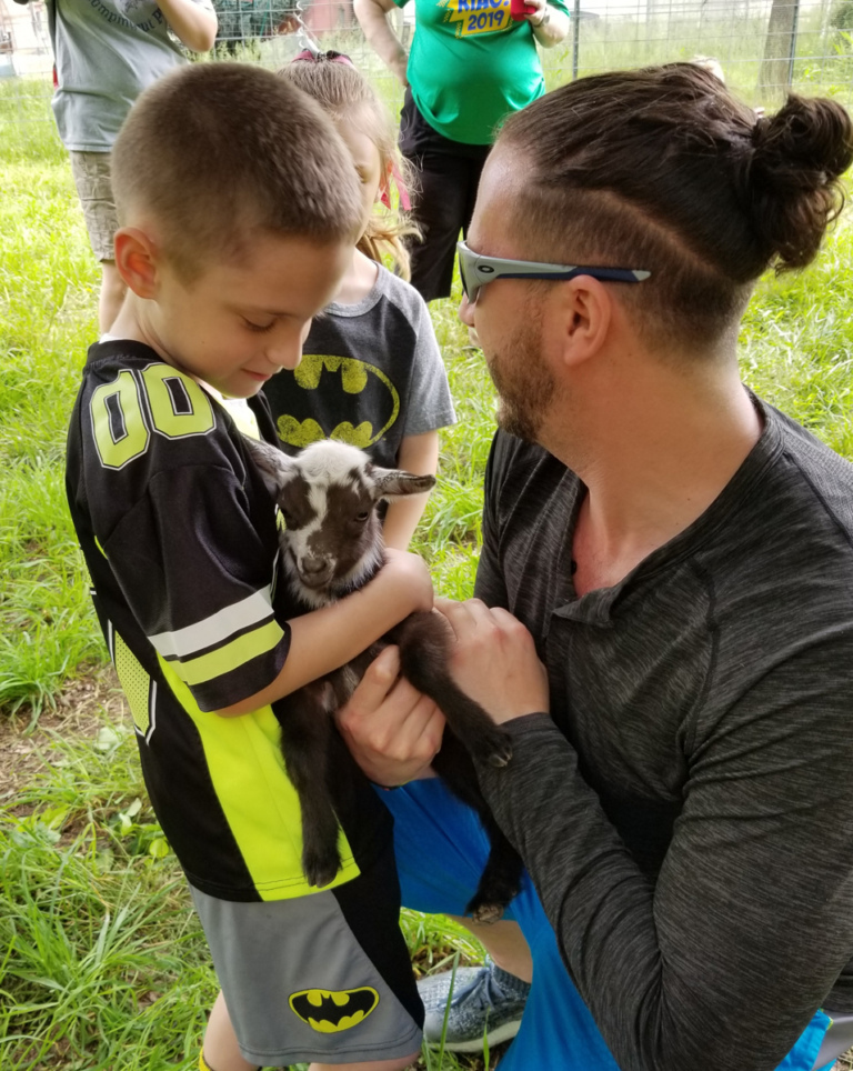 A young boy patient petting a tiny, two-week old goat that is being held by a sponsor team member