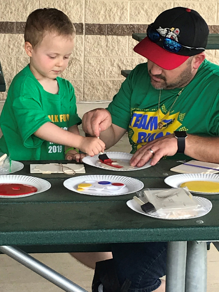 A father and young son painting pieces of a wood bird house