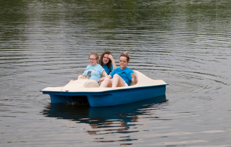 Three young women paddle boating