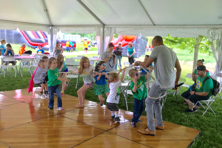 A group of children playing tug of war with the DJ at the Camp Save-A-Limb Festival