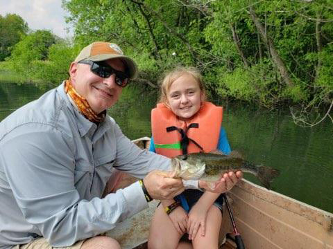 Dr. Standard with a young girl patient in a life jacket in a boat on a lake showing off the fish she caught