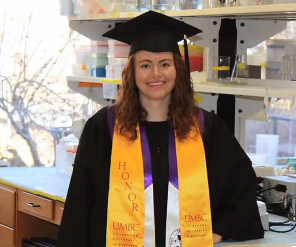 Carly in her graduation cap and gown in a science lab