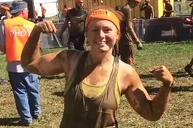 Carly wearing muddy clothes and showing off her muscles at Tough Mudder