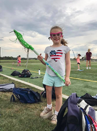 Charlotte dressed in gear for Lacrosse camp with a shoe lift