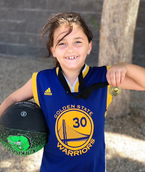 Gracie holding a basketball and a medal after she was cleared to play basketball again