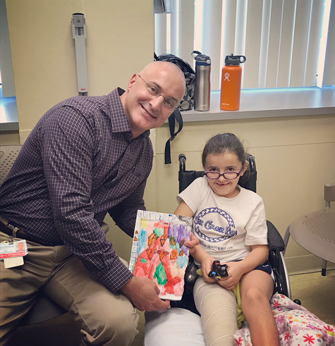 Gracie with Dr. Standard holding artwork she made for him after super knee surgery; Gracie is in a wheelchair with a cast