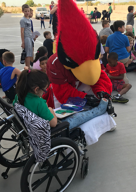 Gracie in a wheelchair with the Arizona Cardinals' mascot signing her cast