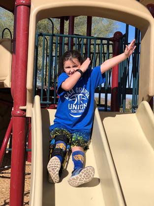 Gracie wearing a leg brace on a playground sliding board