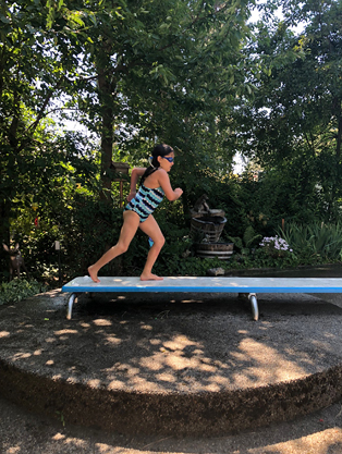 Gracie running on a diving board at a swimming pool 9 months after surgery no longer needing a leg brace