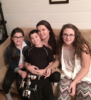 Jackson wearing an external fixator sitting with his mom and sisters