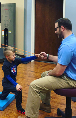 Jadon doing physical therapy with resistance bands