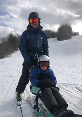 Jadon adaptive skiing on a snowy ski slope