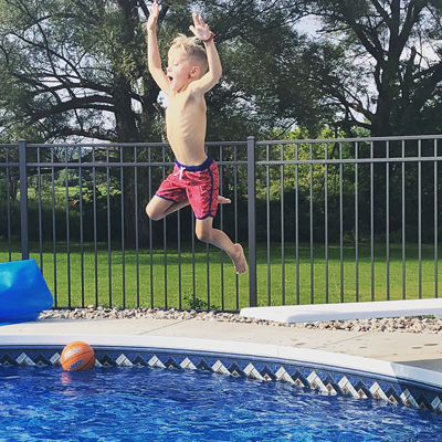Jadon jumping high in the air at a swimming pool